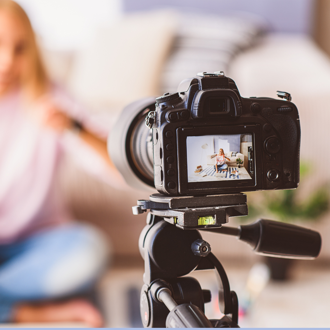 A video camera on a tripod recording a women that is sitting on her couch.